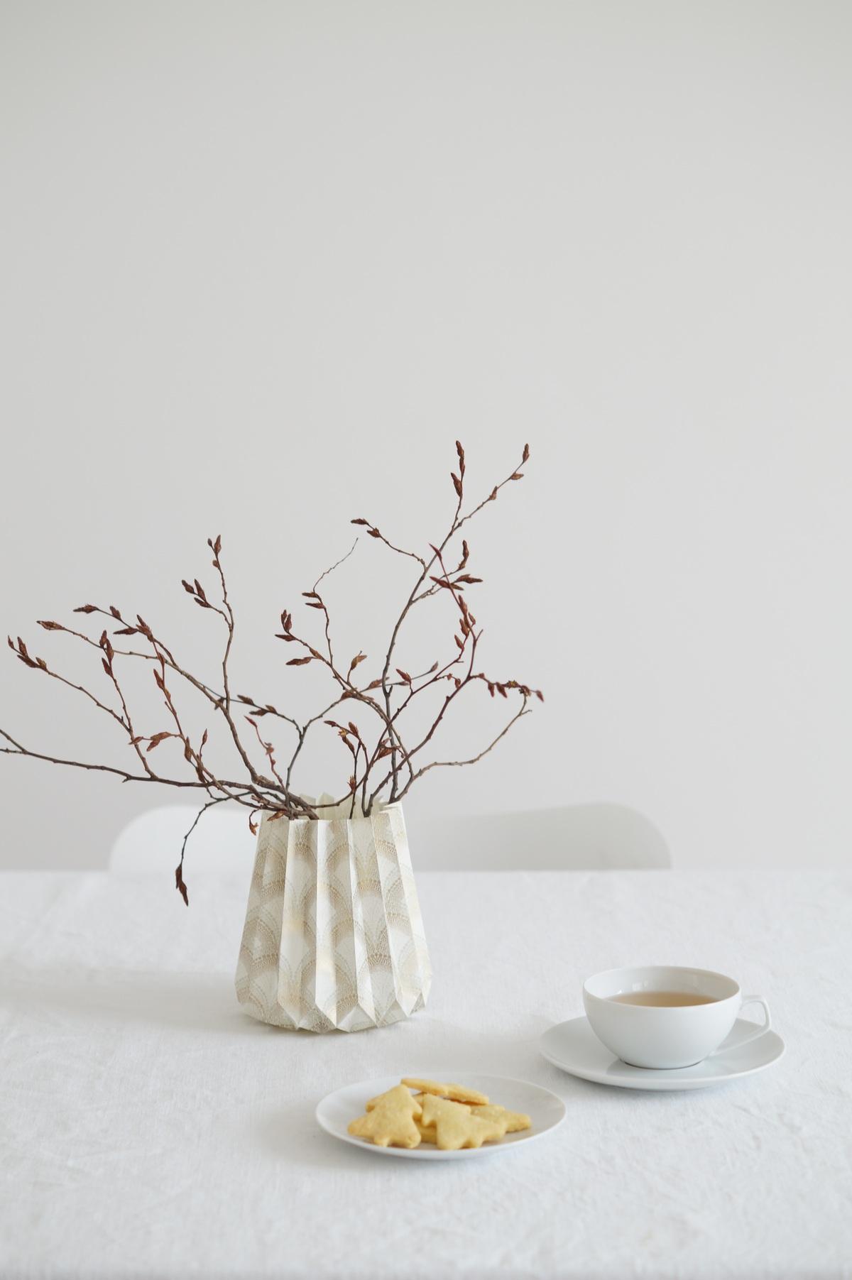Weißes Porzellan und Vasenhülle in gold/weiß
